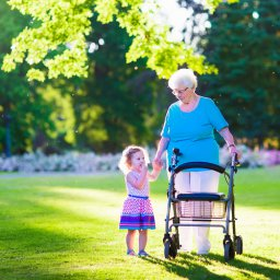 Happy senior lady with a walker or wheel chair and a little toddler girl grandmother and granddaughter enjoying a walk in the park. Child supporting disabled grandparent.